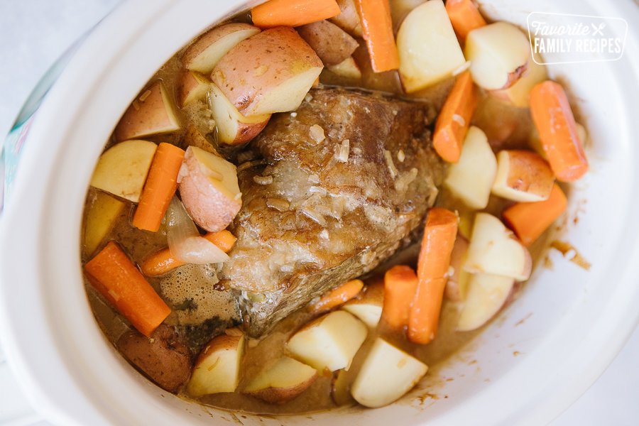 Beef Roast in a white crock pot surrounded by vegetables