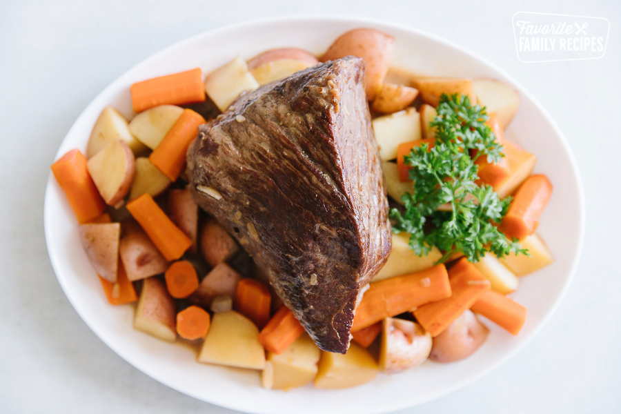 Crock Pot Roast served on a white platter with potatoes and carrots