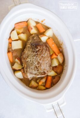 White Crock pot filled with a beef roast, potatoes, carrots, and onions