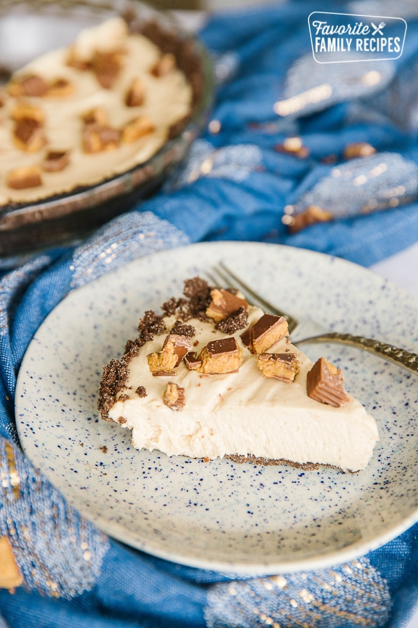 Side view of a slice of Creamy Peanut Butter Pie with a whole pie in the background