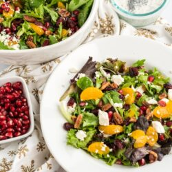 Christmas Salad in a white bowl with a bowl of pomegranate seeds