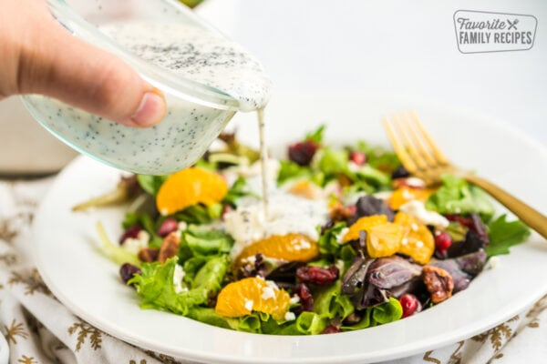Poppyseed dressing being poured over a salad