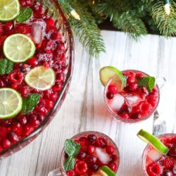 Three punch glass filled with holiday punch and a lime wedge on the side