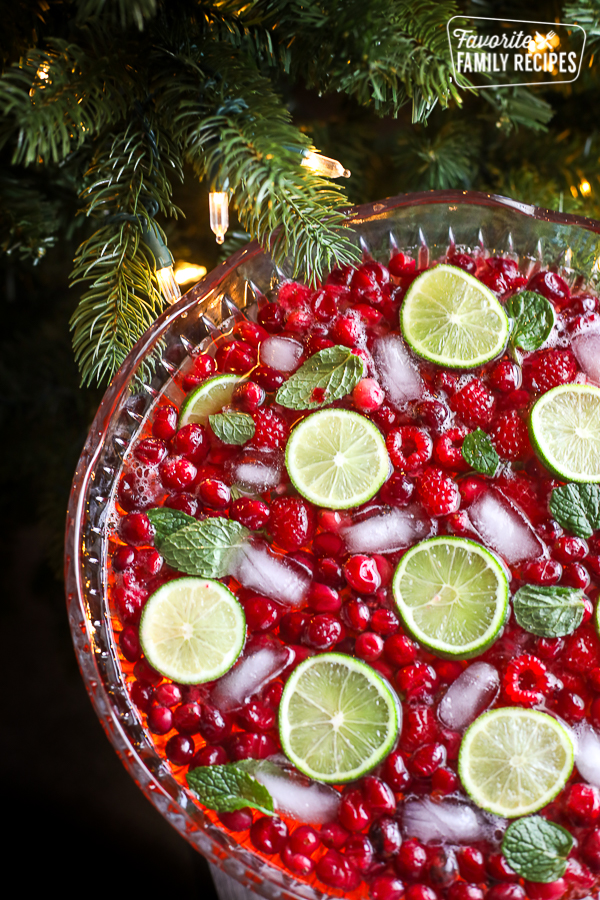 A holiday punch bowl filled with punch, raspberries, cranberries, mint, and fresh lime slices