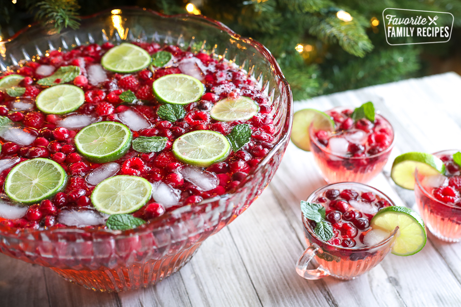Holiday punch in a punch bowl with three clear glass cups of punch to the side