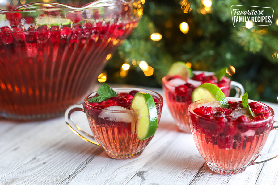 Red Holiday punch in a punch bowl with glass cups filled with holiday punch to the side