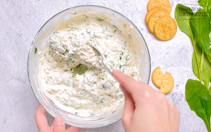 Mixing spinach dip ingredients together in a large bowl
