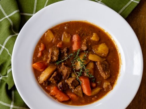 A bowl of instant pot beef stew on a wooden table with a green napkin next to it