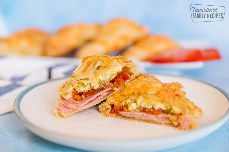 A breakfast hand pie filled with eggs, ham, tomatoes, and green chiles on a blue plate.