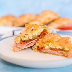 A ham and egg breakfast hand pie on a white plate with a blue background