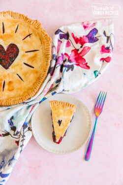 A full berry pie and a sliced piece of berry pie