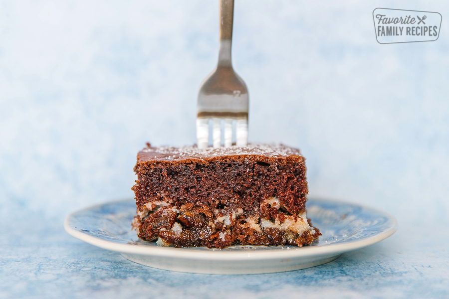 A piece of german chocolate cream cake on a blue plate with a fork in it