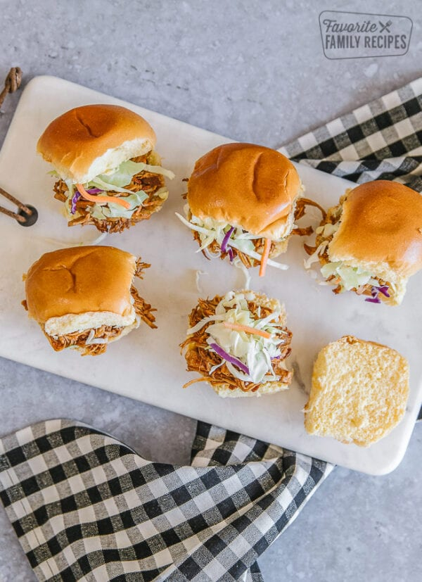 Pulled pork sliders on a marble tray with a black and white checkered napkin underneath