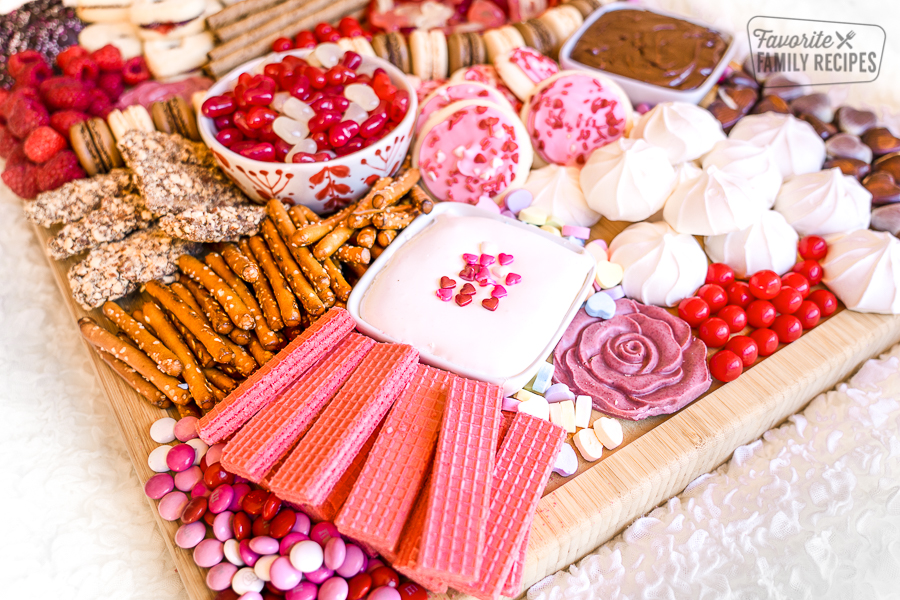 dessert charcuterie board with cookies, candies, and pretzel sticks