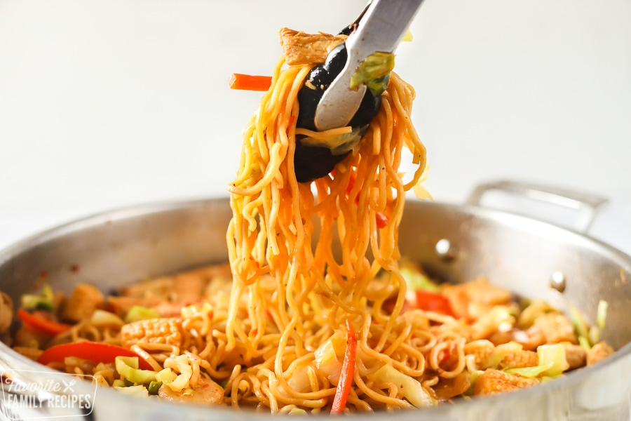 Yakisoba in a skillet being served with tongs
