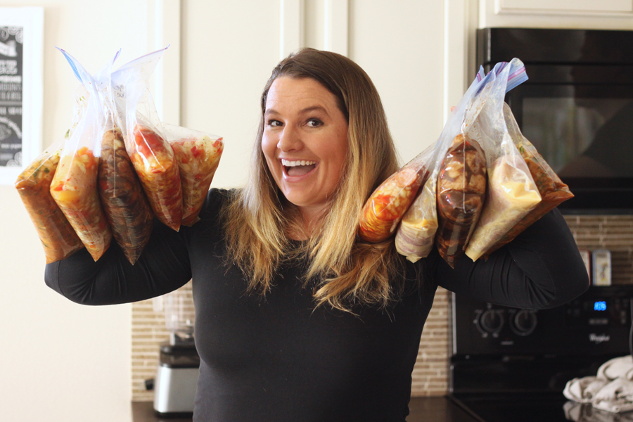 Erica holding ten freezer meals in bags