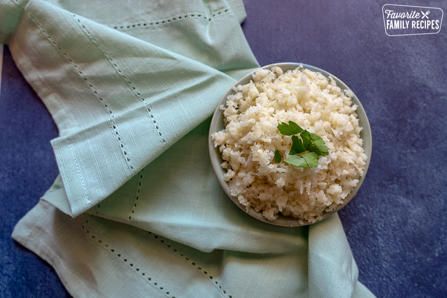 A bowl of cauliflower rice on a blue background.