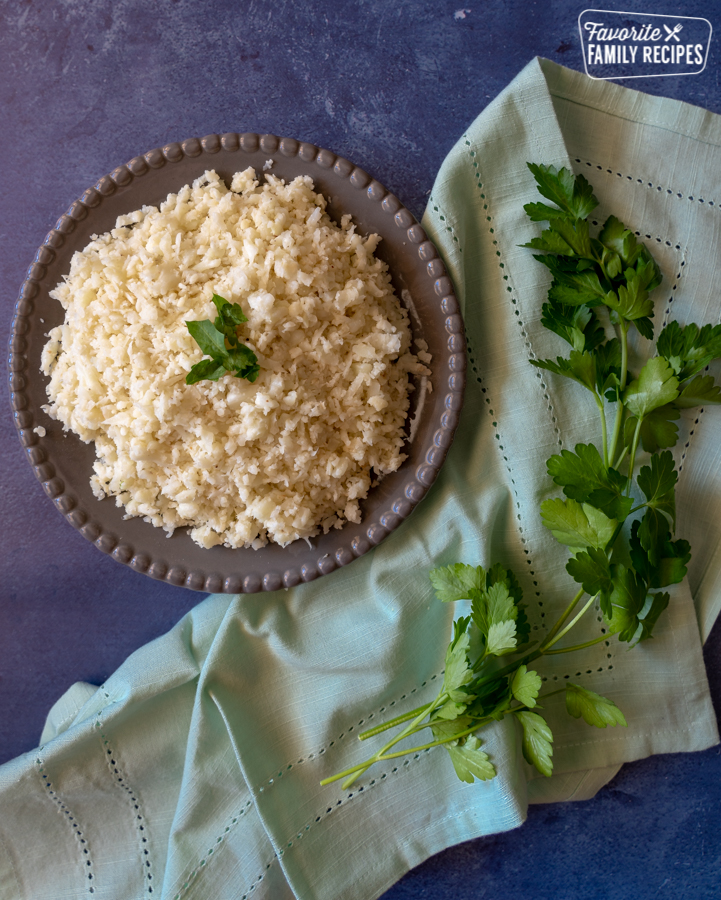 A plate of cauliflower rice on a blue background with parsley scattered around the plate.