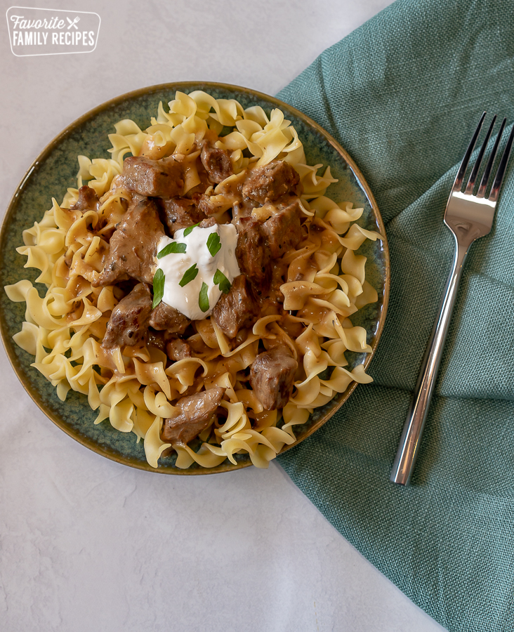 Egg noodles on a blue plate topped with beef stroganoff sauce, sour cream, and parsley