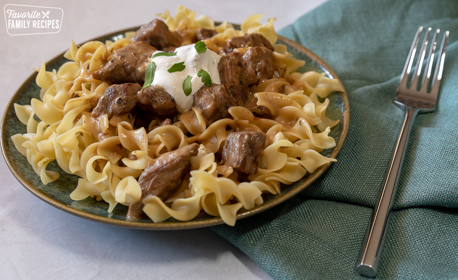Beef Stroganoff on a blue plate topped with sour cream and parsley leaves.