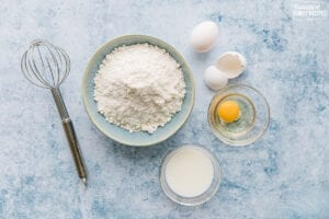 A whisk, A bowl of basic cake mix, an egg, and a bowl of milk on a blue background.