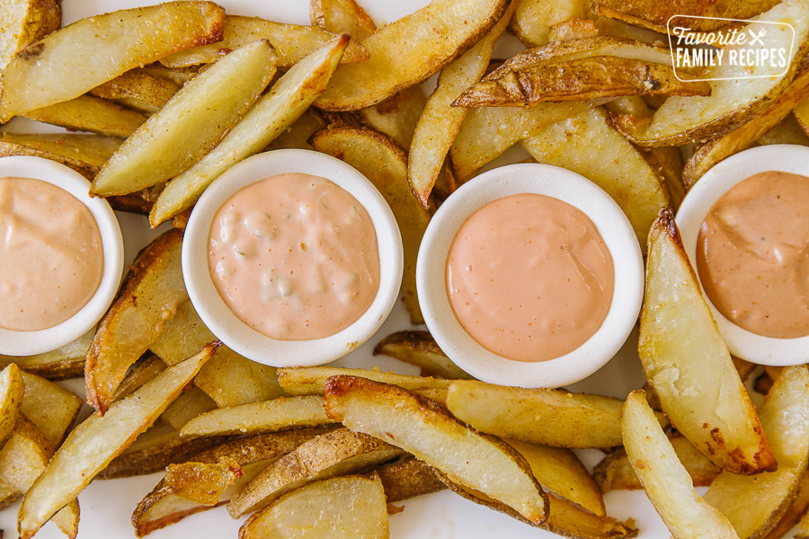 Four kinds of fry sauce on a platter filled with potato fries
