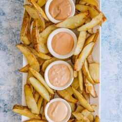 Four kinds of fry sauce on a bed of French fries