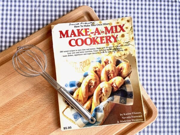 A cookbook called Make A Mix Cookery on a cutting board.