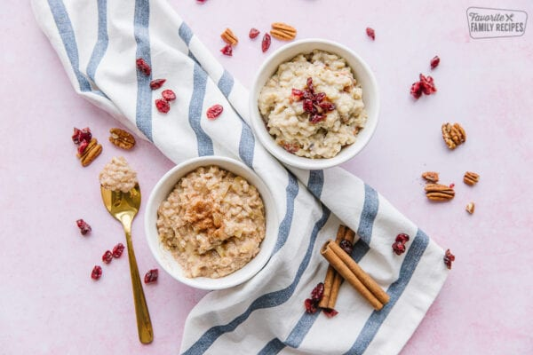 Two bowls of oatmeal on a striped tea towel