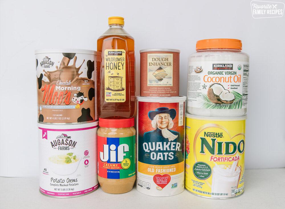 Long term food storage items on a table - dry milk, honey, oats, oil