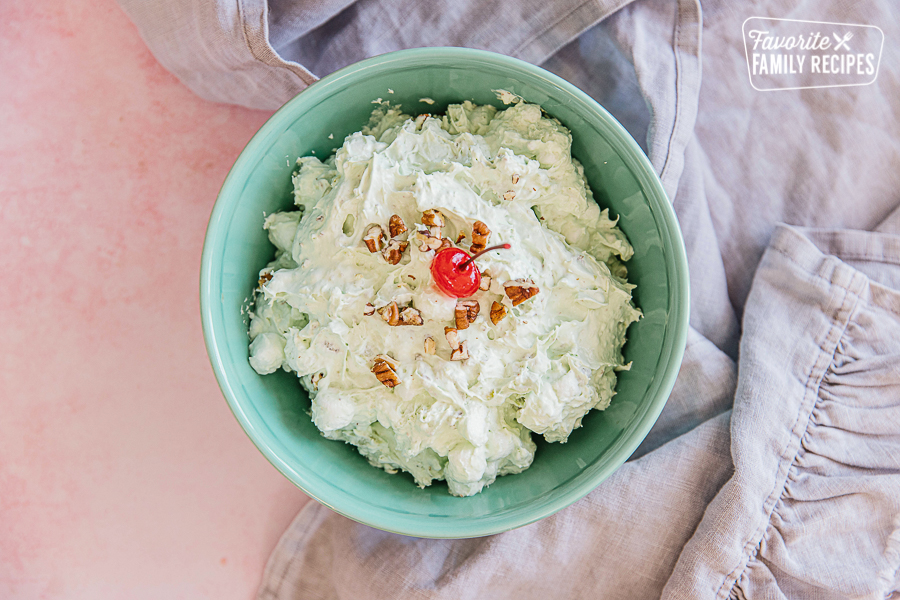 Watergate Salad in a green bowl, topped with pecans and a cherry.