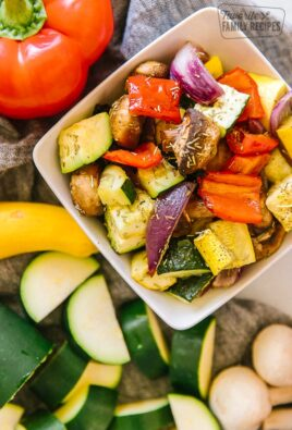 A close up view of oven roasted vegetables in a white bowl
