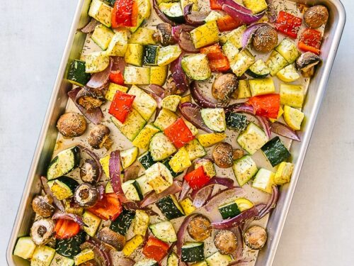 Oven roasted vegetables sprinkled with rosemary on a baking pan