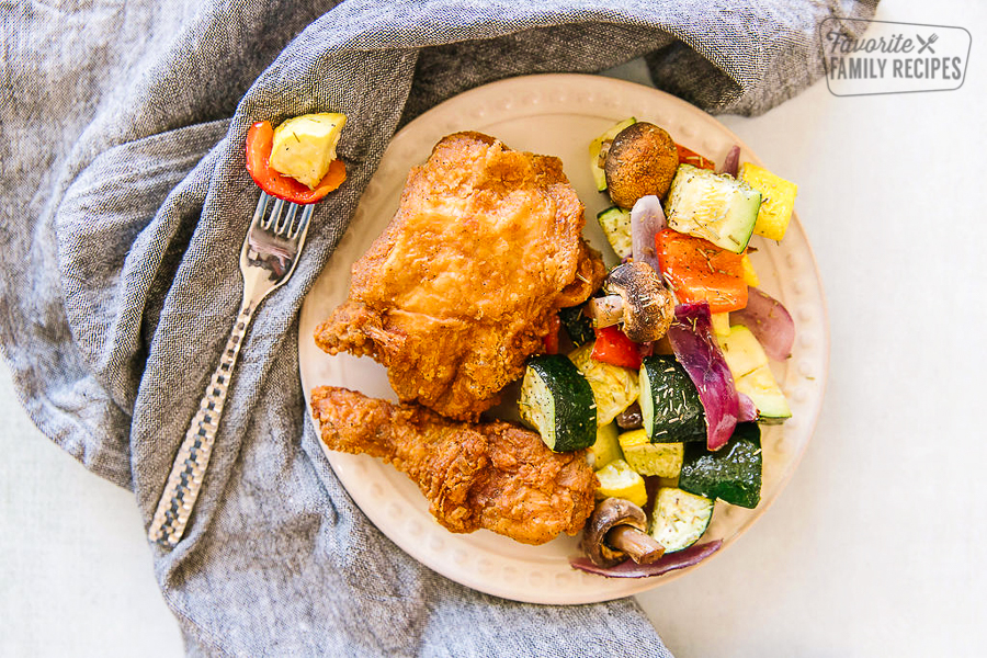 Fried chicken and oven roasted vegetables on a serving plate