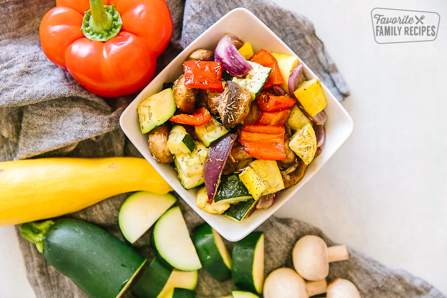 Oven roasted vegetables in a square dish with fresh vegetables on the side