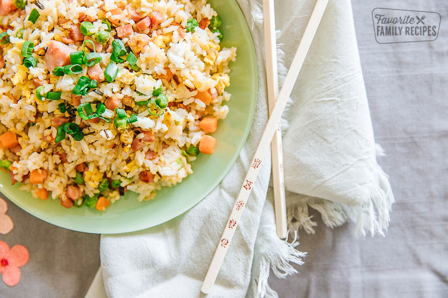 Up close look at a bowl of ham fried rice with chopsticks on the side