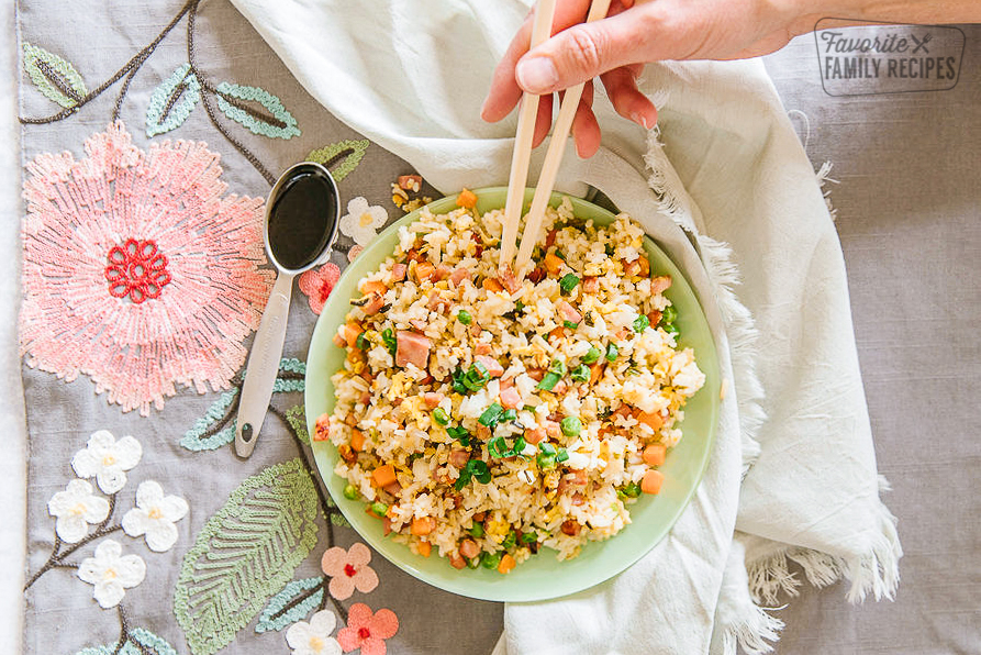 Ham Fried Rice in a bowl with soy sauce in a teaspoon on the side