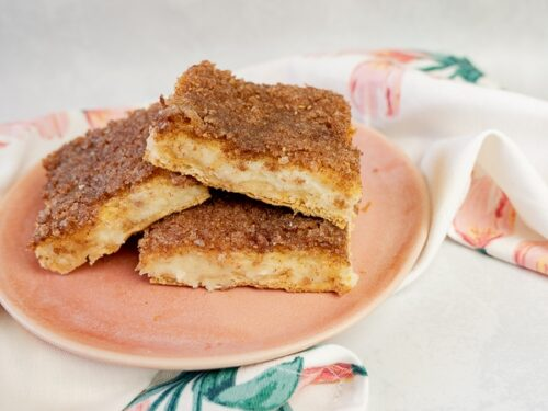 A stack of sopapilla cheesecake bars on a pink plate