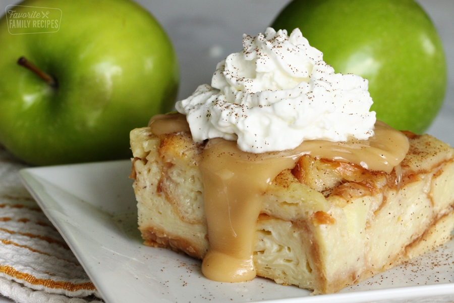 A slice of bread pudding on a plate topped with caramel sauce and whipped cream