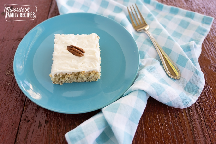 A slice of banana cake with cream cheese frosting topped with a pecan on a blue plate with a fork and a blue and white checked napkin.