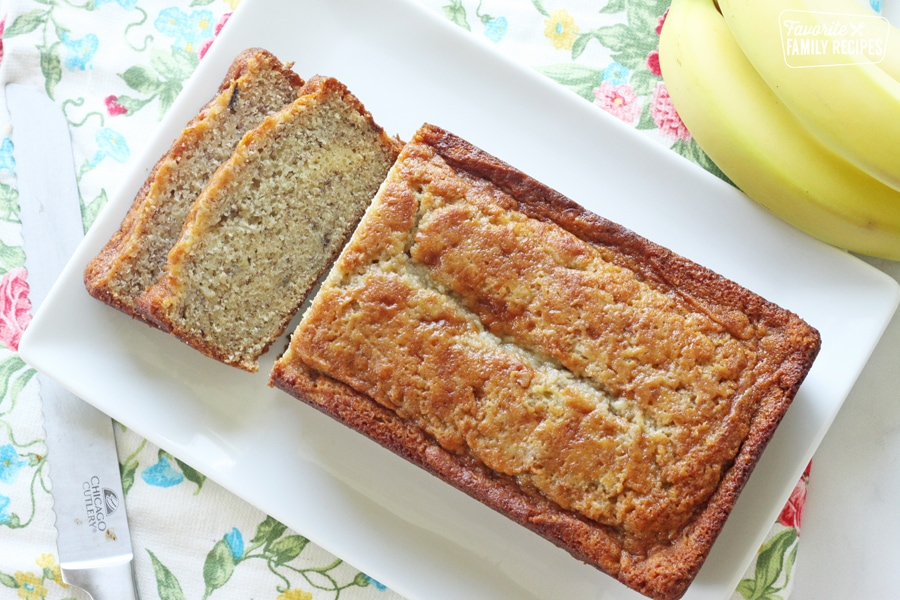 Banana bread on a plate next to bananas