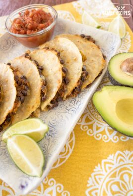 Black bean tacos stacked up on a plate with limes, avocados, and a bowl of salsa.