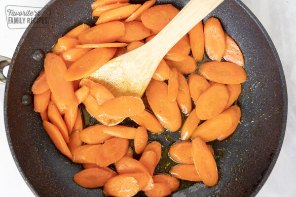 Sliced carrots in a skillet with a wooden spoon