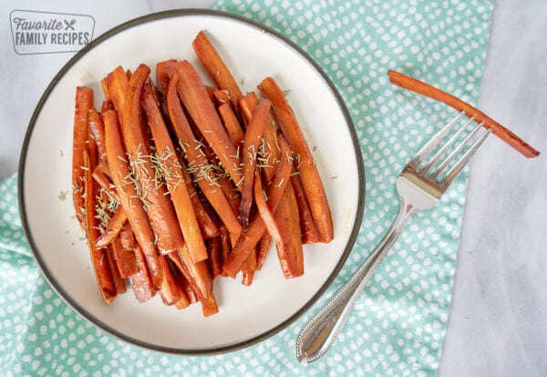 Julienned carrots on a plate with a fork and a blue napkin