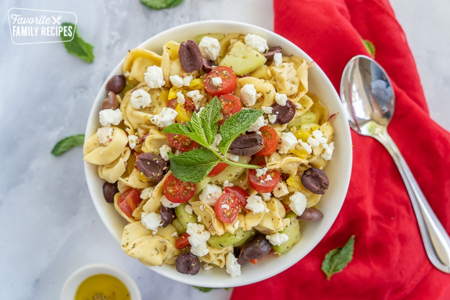 Greek Tortellini Salad in a white bowl with a spoon, a red napkin, and a little bowl of olive oil