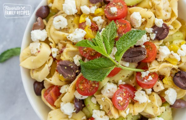 greek tortellini salad topped with a mint leaf