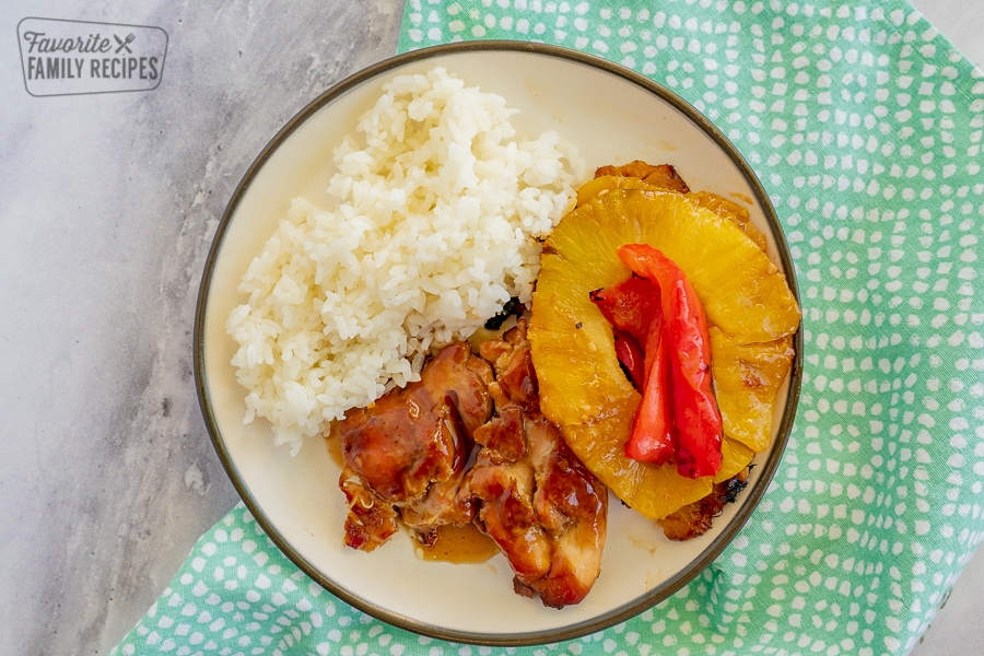 Chicken, pineapple, peppers, onion, and rice on a plate with a blue napkin and a marble background.