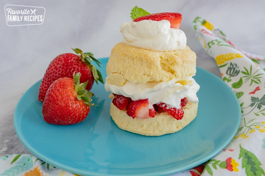Strawberry shortcake on a blue plate on top of a marble countertop