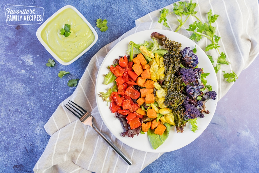 rainbow buddha bowl with creamy avocado dressing on a blue background with a fork