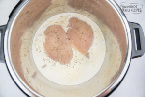 Raw chicken breasts in Alfredo sauce in the Instant Pot